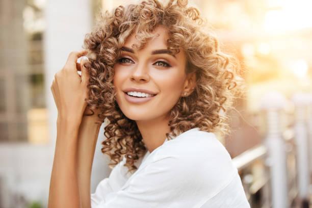 vrolijke blonde vrouw glimlachend en genietend van buiten tijdens een prachtige zonsondergang - blond curly hair stockfoto's en -beelden