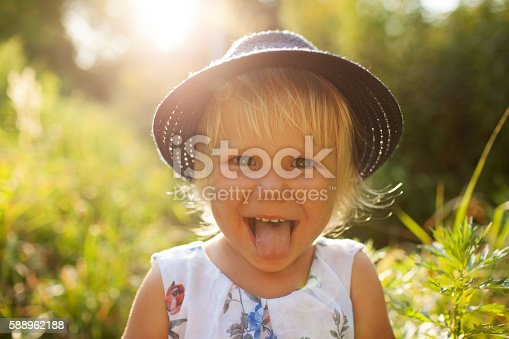 istock Cheerful blonde girl in a blue hat shows tongue 588962188