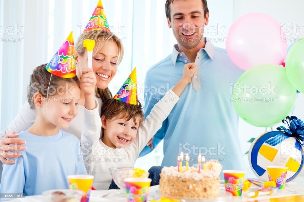 Cheerful boy celebrating birthday with sister and parents. royalty-free stock photo