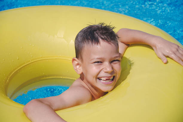 cheerful boy enjoys floating on inflatable ring in swimming pool - children play water park stock photos and pictures