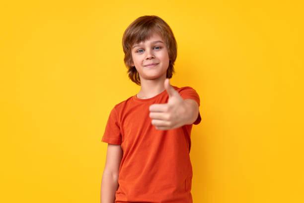 Cheerful boy gesturing thumb up stock photo