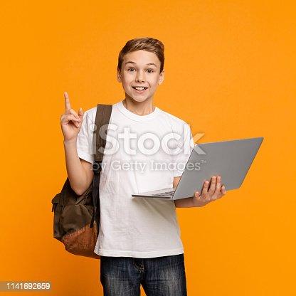 Adorable little boy having idea using laptop, orange studio background