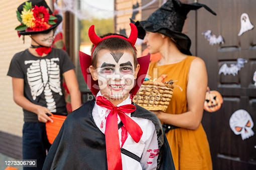 Cheerful boy in halloween costume looking at you against young woman in yellow dress and hat holding basket with treats and his friend