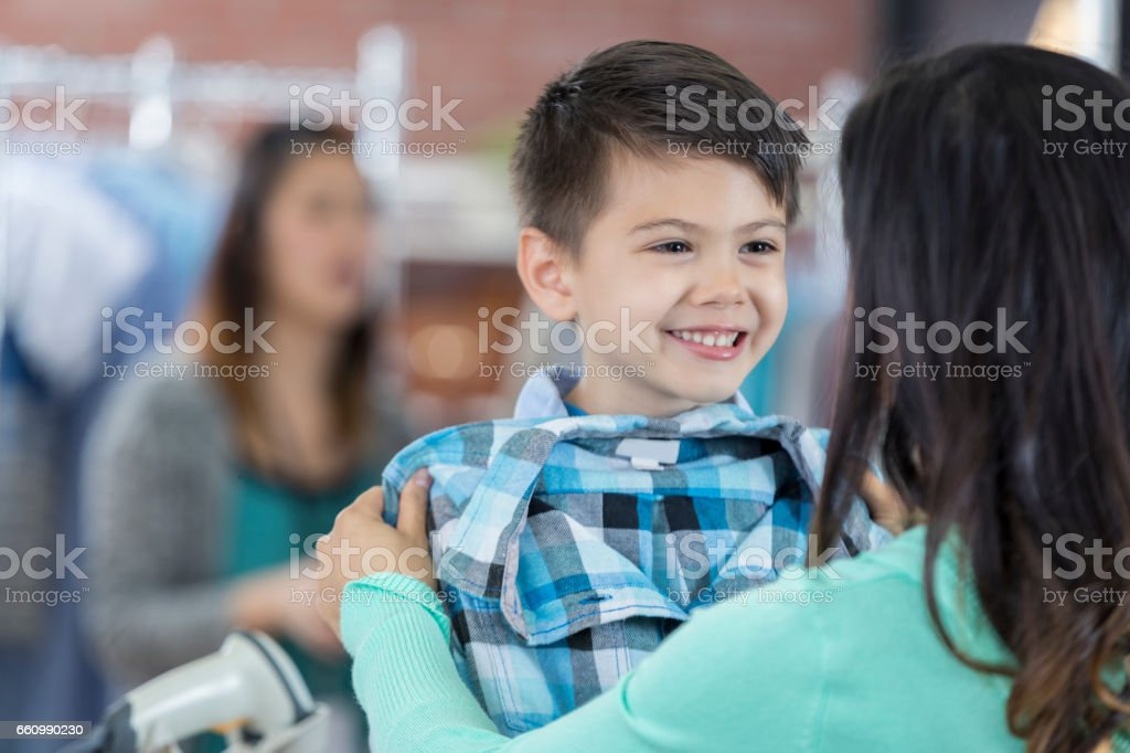 Cheerful boy shops with his mother stock photo
