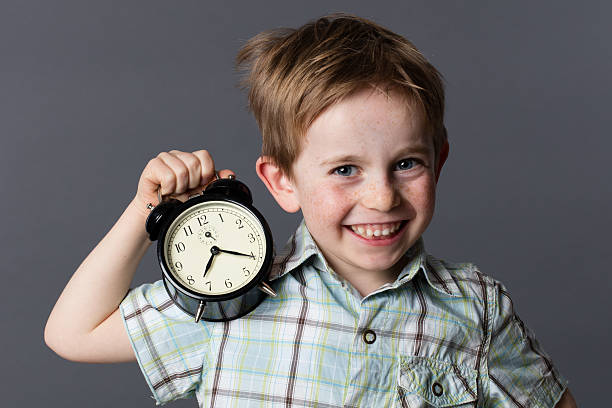 cheerful boy showing an alarm clock for playful time concept – Foto