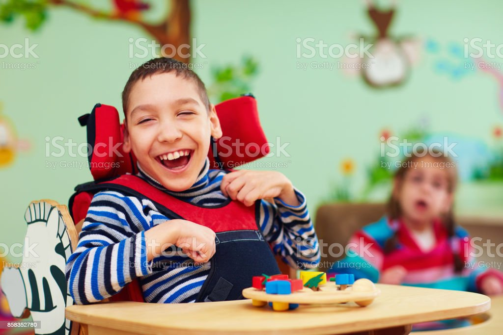 cheerful boy with disability at rehabilitation center for kids with special needs stock photo