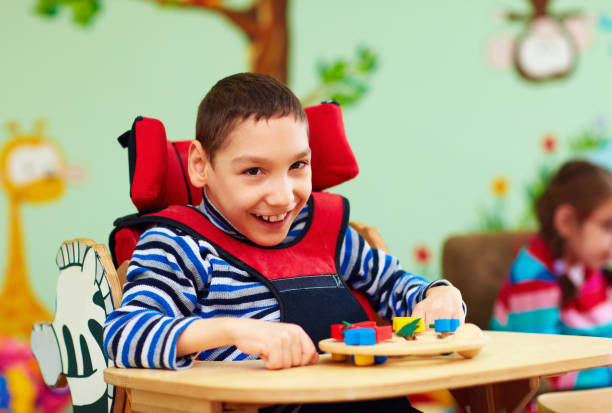 cheerful boy with disability at rehabilitation center for kids with special needs - foto stock