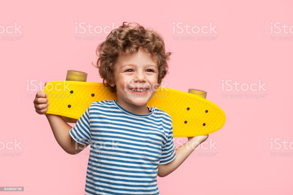 Cheerful boy with longboard on pink stock photo