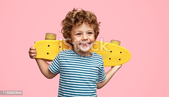 Funny little boy with yellow skateboard smiling and looking away while standing on pink background