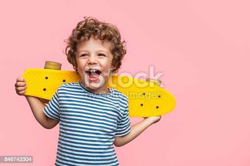 istock Cheerful boy with yellow longboard 846743304