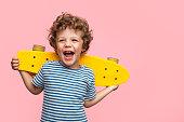 Cheerful boy with yellow longboard