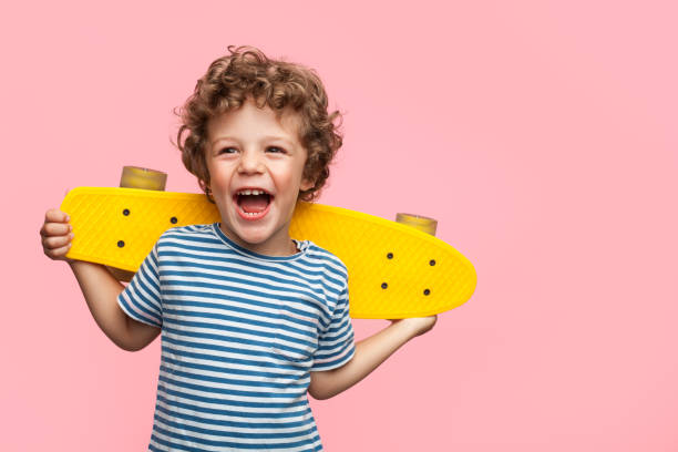 Cheerful boy with yellow longboard stock photo