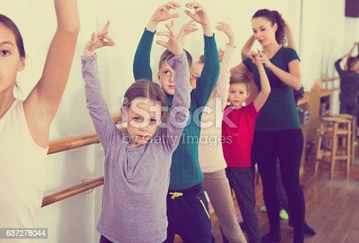 istock cheerful boys and girls rehearsing ballet dance in studio 637278044