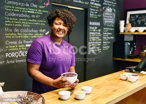 Young woman in her 20s smiling towards camera, holding bowl of food, working and serving