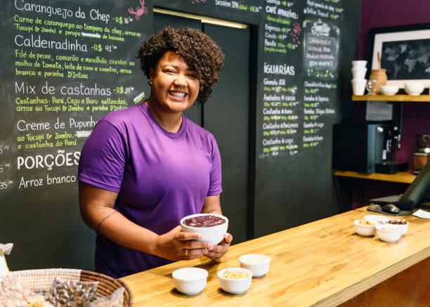 fröhlichen brasilianerin tresen in açai-café - küche lila stock-fotos und bilder