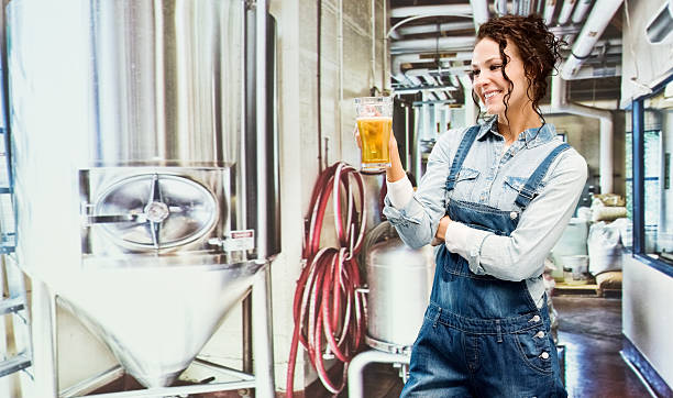 Cheerful brewmaster holding beer glass stock photo