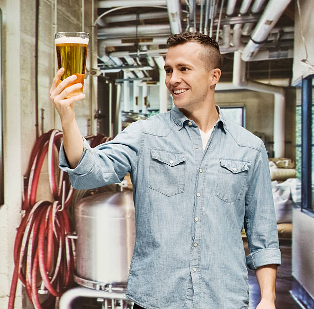 Cheerful brewmaster holding drinking glass stock photo