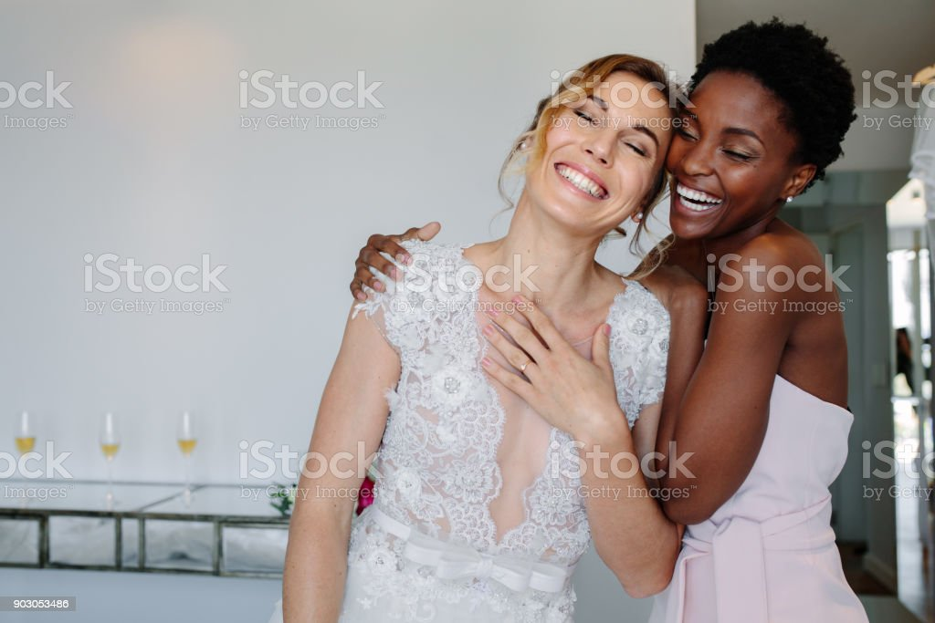 Cheerful bride and bridesmaid on the wedding day stock photo
