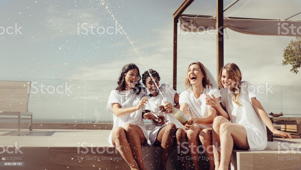 Cheerful bride and bridesmaids celebrating hen party stock photo