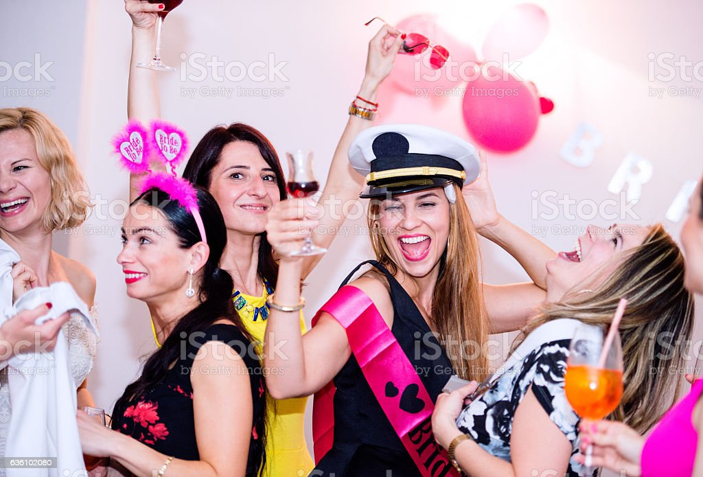 Cheerful bride and bridesmaids celebrating hen party with drinks stock photo