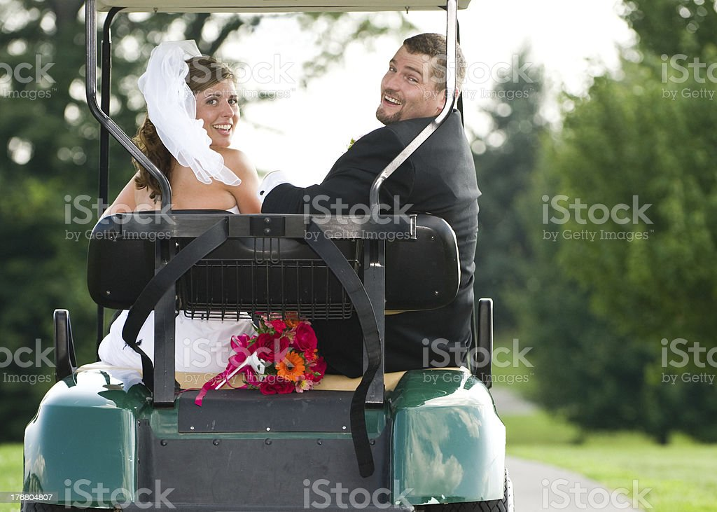 Cheerful Bride and Groom on a Golf Cart stock photo