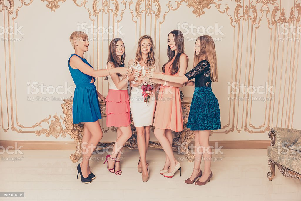 Cheerful bride with her bridesmaids celebrating hen-party stock photo