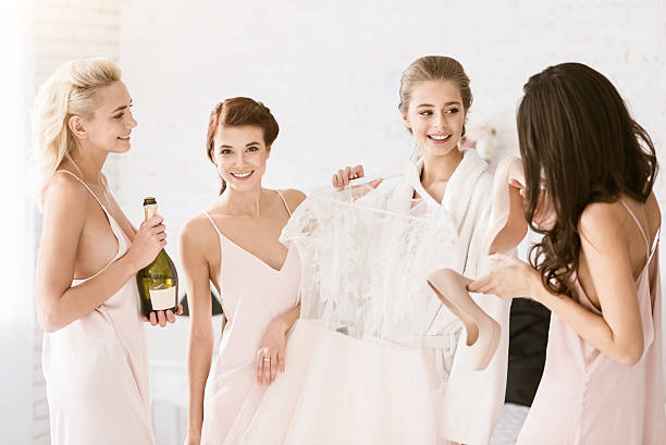 Cheerful bridesmaids helping the bride to get ready for wedding stock photo