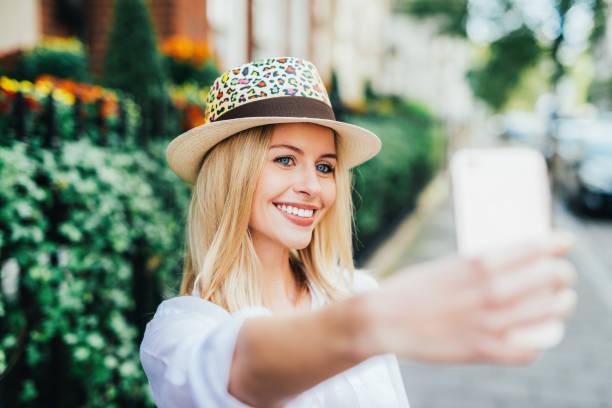 mulher de cabelo loiro britânico alegre tomando selfies durante as férias de cidade - girl power provérbio em inglês - fotografias e filmes do acervo