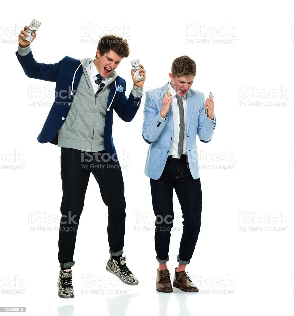 Cheerful brothers cheering with money stock photo