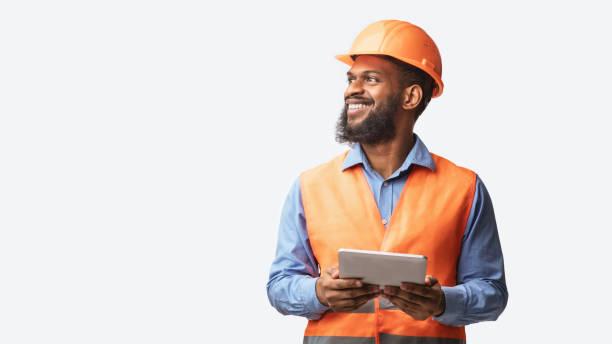 Cheerful Builder Holding Digital Tablet Posing On White Studio Background stock photo