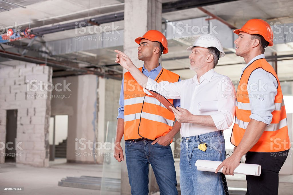 Cheerful builders are working on plan of building stock photo