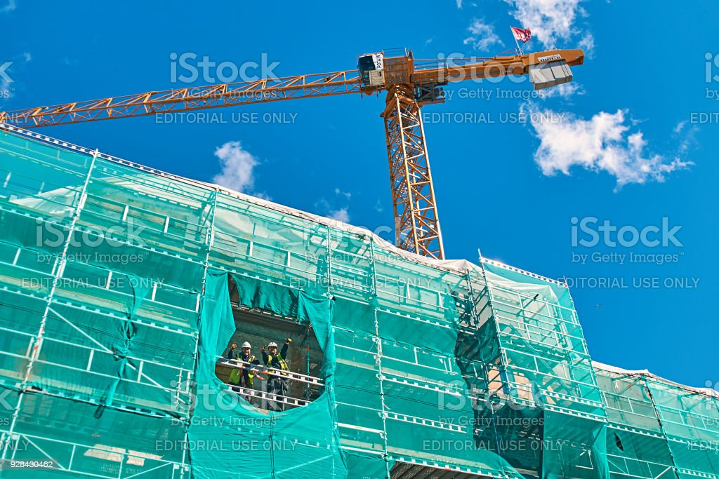 Cheerful builders workers gesture while working on the construction site stock photo