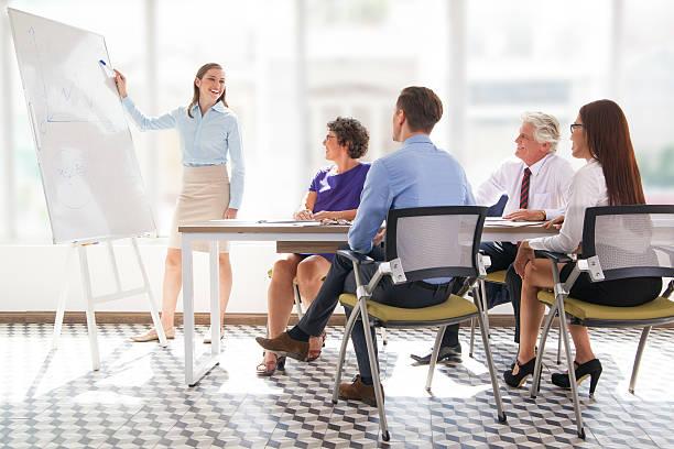 cheerful business coach explaining strategy - présentateur photos et images de collection
