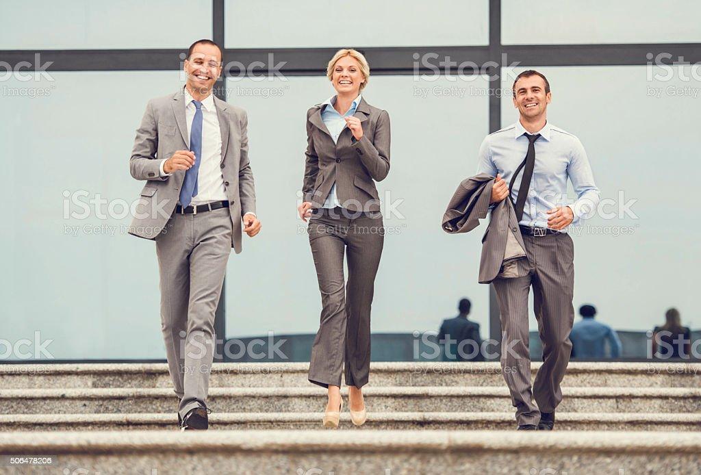 Alegre colegas de trabalho para baixo para corrida em escadas. - foto de acervo