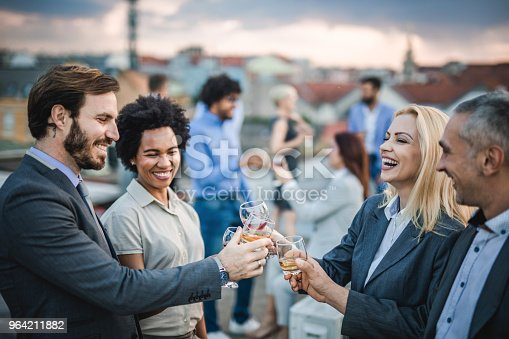 Group of happy business people having fun while toasting with alcohol at the outdoor party.