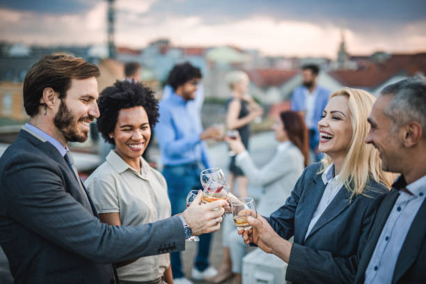 Cheerful business colleagues toasting with alcohol at the outdoor party. stock photo