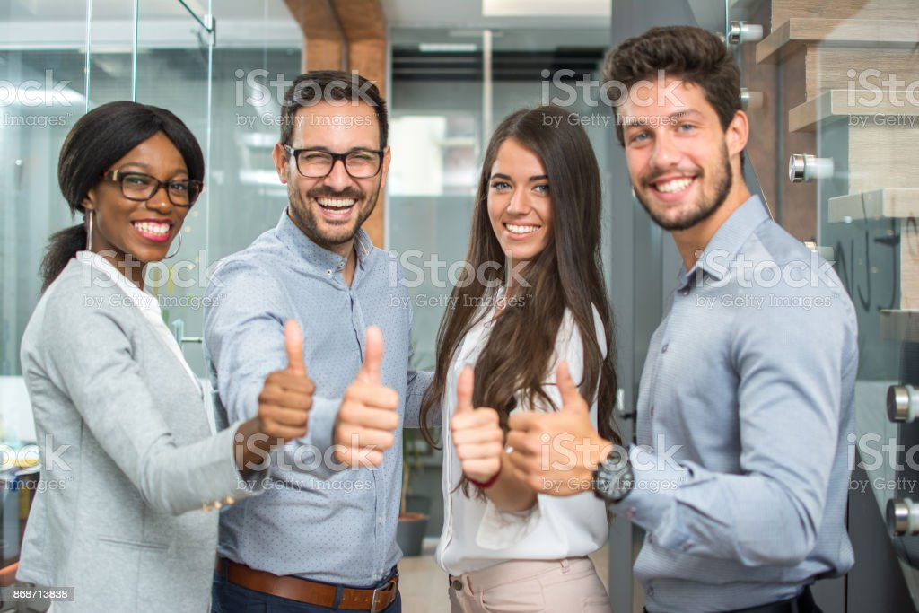 Cheerful business group showing thumbs up. stock photo