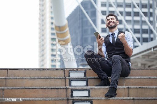 istock Cheerful Business Man Celebrating Success with mobile phone sitting on the stairs in urban city outdoors, looking up , good news,yes, raising hands,excited,Fulfill,winner , copy space 1139299116