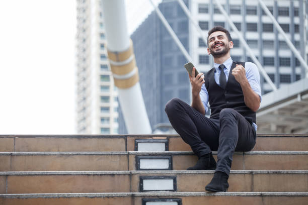 Cheerful Business Man Celebrating Success with mobile phone sitting on the stairs in urban city outdoors, looking up , good news,yes, raising hands,excited,Fulfill,winner , copy space stock photo