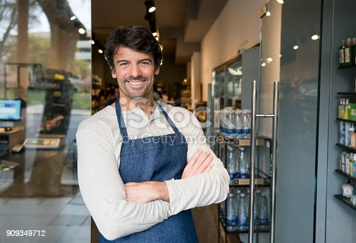 istock Cheerful business owner of an organic market standing at the entrance smiling 909349712