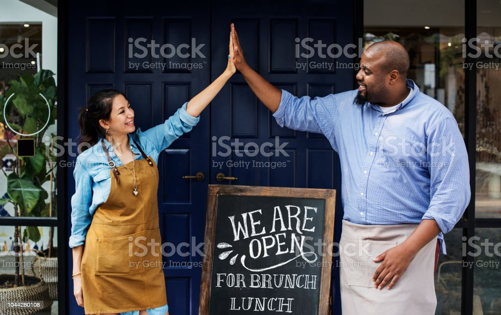 Cheerful business owners standing with open blackboard stock photo