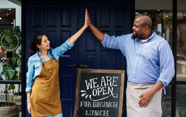 cheerful business owners standing with open blackboard - owner stock pictures, royalty-free photos & images