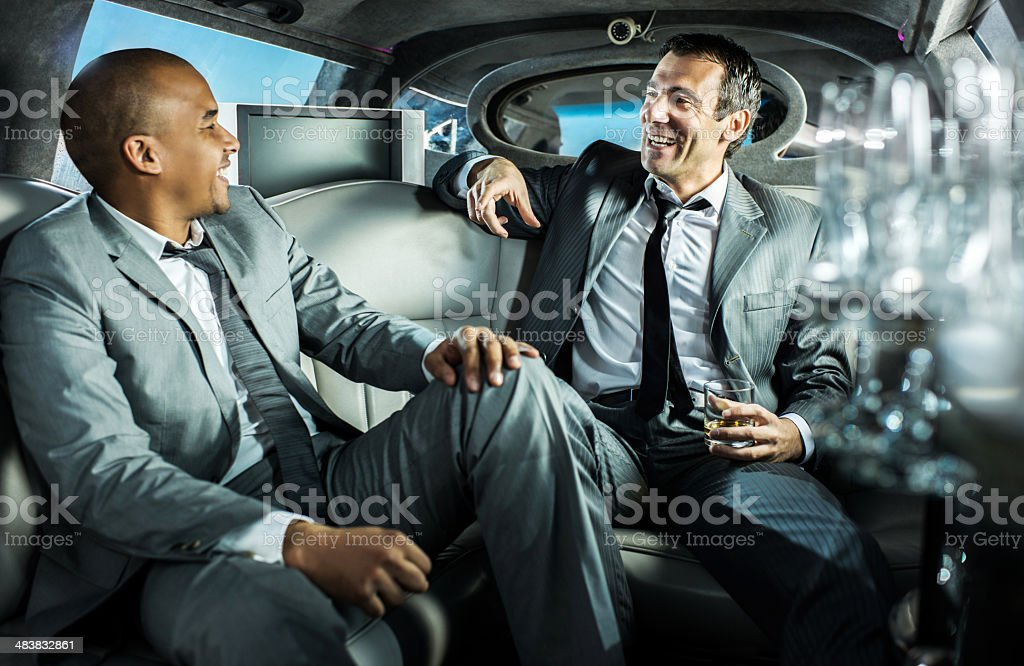 Cheerful business people in a limousine. stock photo