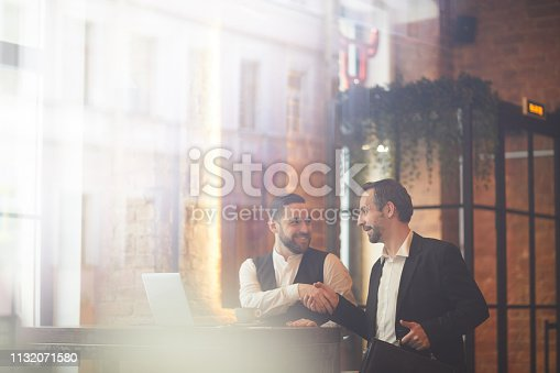 Portrait of two smiling business people shaking hands after successful meeting shot from behind glass, copy space