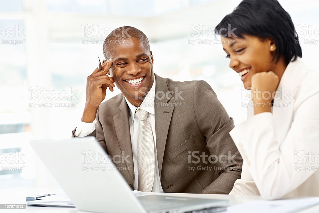 Cheerful business people working on a laptop at office royalty-free stock photo