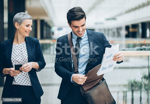 Cheerful business persons walking together inside business building