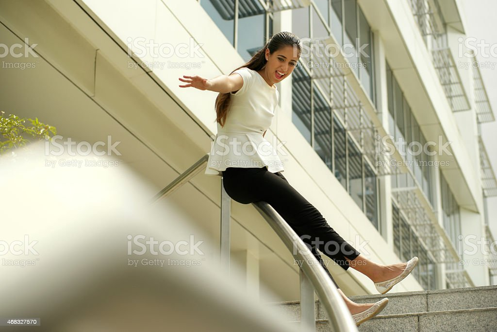 Cheerful Business Woman Going Downstairs Sliding On Rail For Joy stock photo