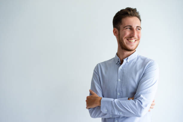 Cheerful businessman enjoying success Cheerful businessman enjoying success. Young man in office shirt folding arms, looking away and smiling. Business success concept young adult stock pictures, royalty-free photos & images