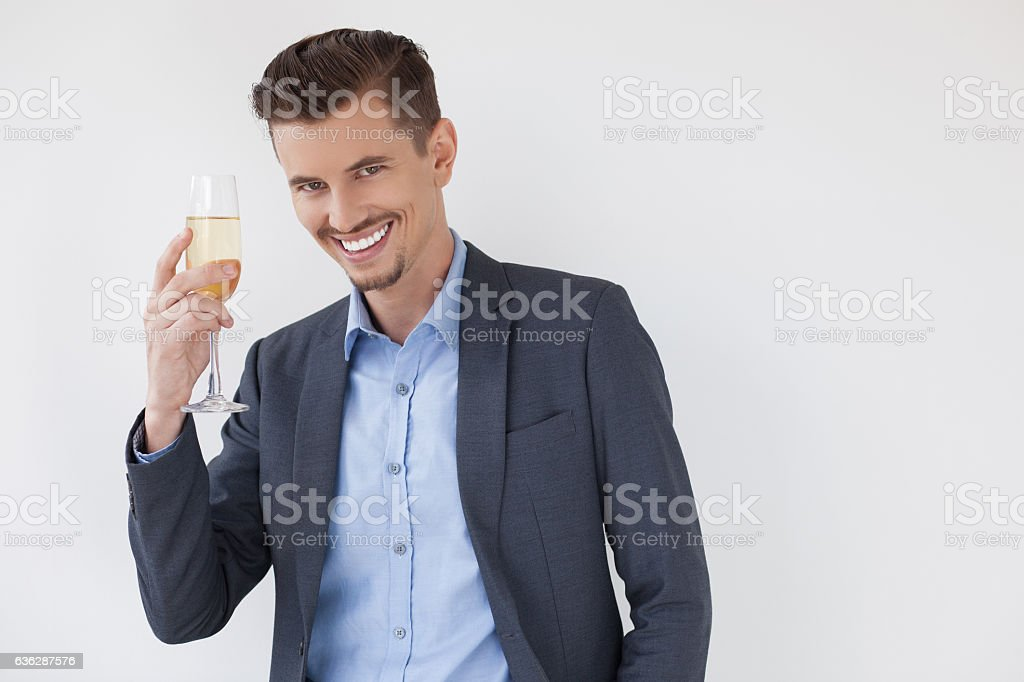 Cheerful businessman giving toast with champagne stock photo