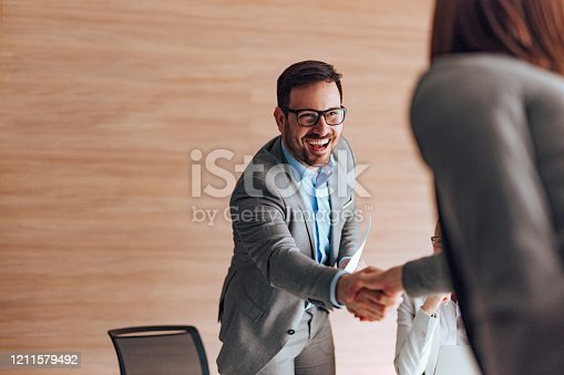 Cheerful businessman greeting job applicant.